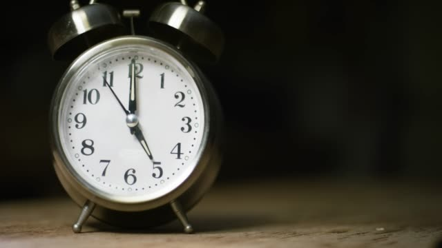A Silver-Colored, Metal, Retro-Style, Analog Alarm Clock at 5:00