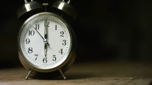 A Silver-Colored, Metal, Retro-Style, Analog Alarm Clock at 6:00
