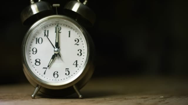 A Silver-Colored, Metal, Retro-Style, Analog Alarm Clock at 7:00