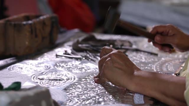 stockvideo's en b-roll-footage met zilverwerk maken. thaise craftman zijn het maken van zilverwerk. het origineel van de zilveren ambachtslieden op wua lai weg, chiang mai. thailand. - hamer handgereedschap