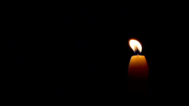 Simple burning candle on a black background, left balck copyspace video