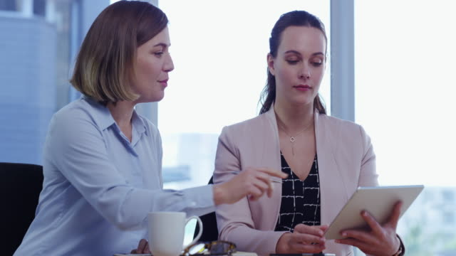 Simplifying the process of project management with smart tech 4k video footage of two young businesswomen using a digital tablet in a modern office employee engagement stock videos & royalty-free footage