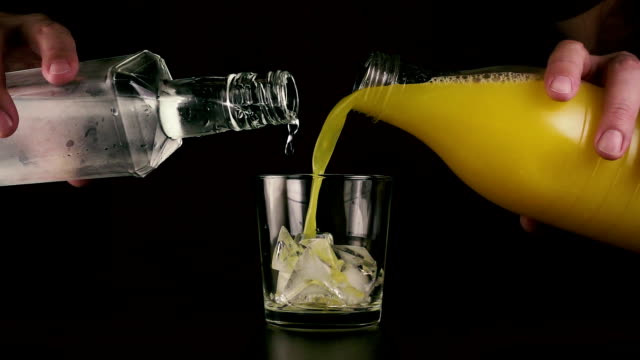 Simultaneously pour into a glass of juice and vodka from a bottle. Slow mo video