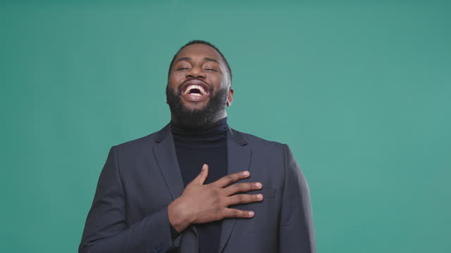 stockvideo's en b-roll-footage met oprechte afro amerikaanse mens in jasje glimlacht rakende borst - afro amerikaanse etniciteit