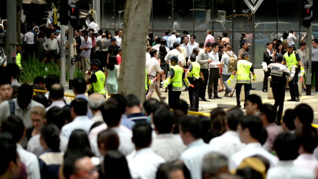 Singapore General Election 2015 Office workers going to attend political rally during lunch break at Raffles Place, Central Business District of Singapore. Policemen and policewomen directing vehicle traffic and crowd outside the venue. police meeting stock videos & royalty-free footage