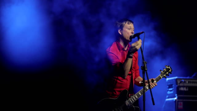 singer playing guitar and singing on stage - cantante video stock e b–roll
