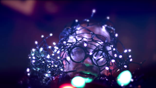 Singing man with christmas lights on head, turns, blinking, glasses, motion video