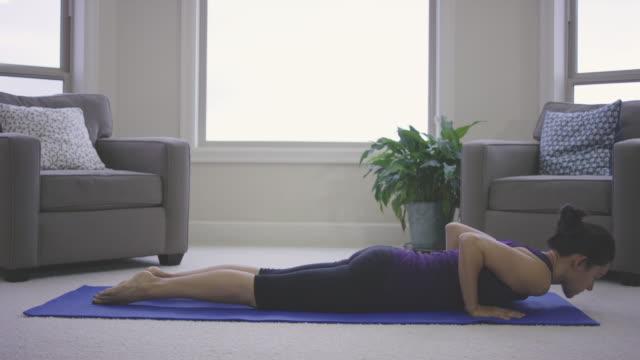 single adult female doing yoga at home - gambe incrociate video stock e b–roll