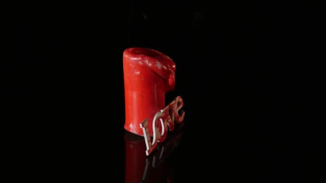 A single burning red candle rotate isolated in front of black background video