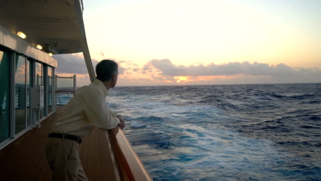 single caucasian adult man looking at sunset from deck of cruise ship - cruise video stock e b–roll