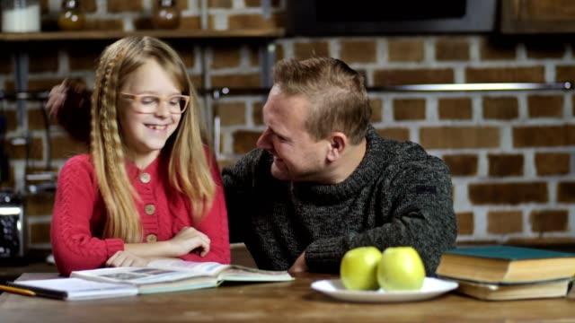 bekar baba kızı evde ev ödevlerinde yardım - çalışma kitabı stok videoları ve detay görüntü çekimi