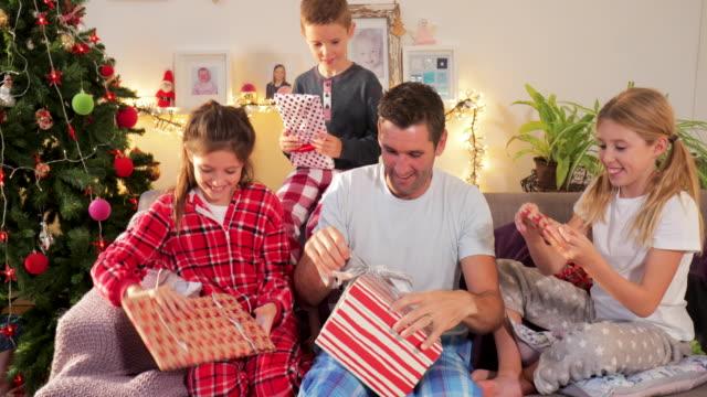 en ensamstående pappa och barn öppning presenterar på jul - christmas gift family bildbanksvideor och videomaterial från bakom kulisserna