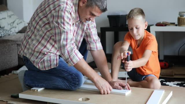 single father is assembling furniture with his kids - narzędzie do pracy filmów i materiałów b-roll