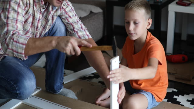single father is assembling furniture with his kids - preadolescente video stock e b–roll