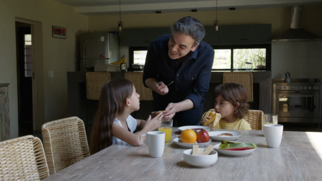 Single father spreading cream cheese on toast for loving daughter while talking to both his kids