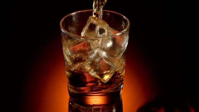 Single glass of whisky bourbon on ice on shiny background video