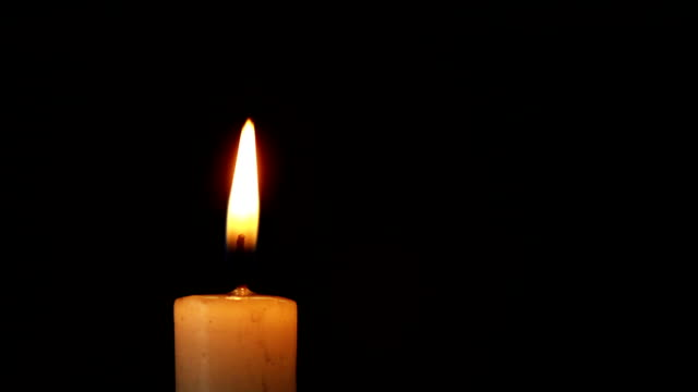 single lit candle with quite flame - lanterna attrezzatura per illuminazione video stock e b–roll
