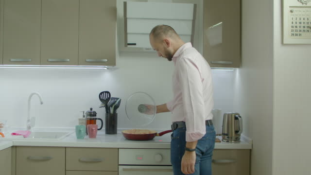 주방에서 아침 오믈렛을 요리 하는 한 남자 - 한 명의 중년 남자만 스톡 비디오 및 b-롤 화면