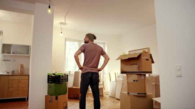enda man flyttar in i ny lägenhet. - flyttlådor bildbanksvideor och videomaterial från bakom kulisserna