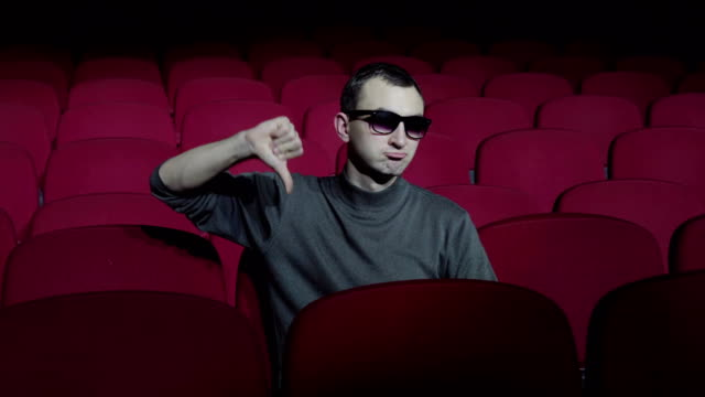 Single man sitting in comfortable red chairs in dark cinema theater and showing thumbs down video