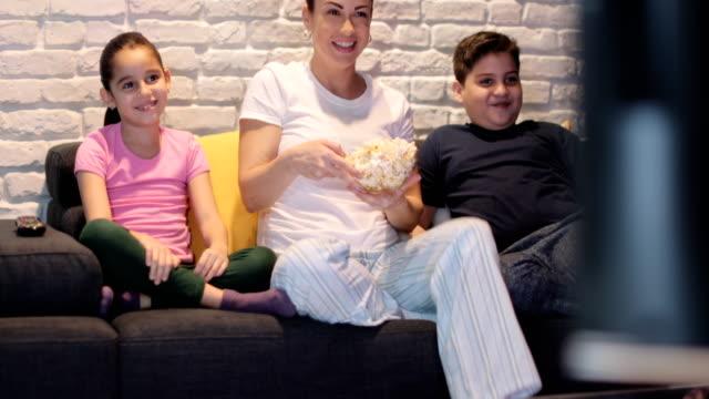 vídeos y material grabado en eventos de stock de madres solteras y los niños viendo la televisión en la noche - family watching tv