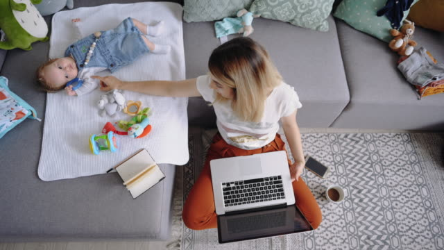 single mother working from home and playing with her baby boy - ultra high definition television filmów i materiałów b-roll