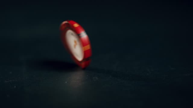 A single red poker chip spins in slow motion until it falls down. Extreme close up.