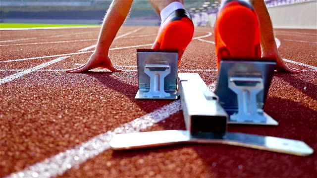 vidéos et rushes de sprinter unique athlétisme dans un stade à partir hors du bloc, le mouvement lent - starting block