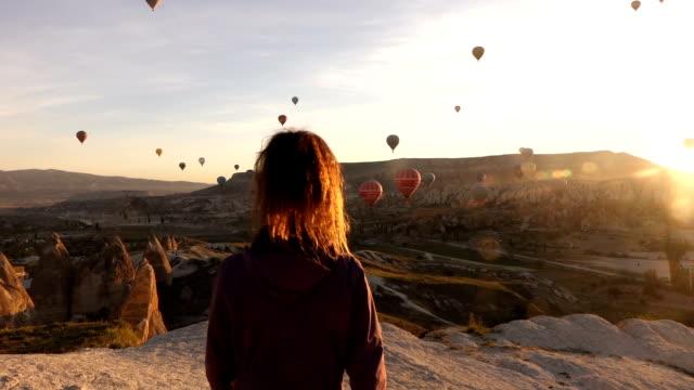 singola donna che cammina mentre guardando mongolfiere in cappadocia - posizione corretta video stock e b–roll