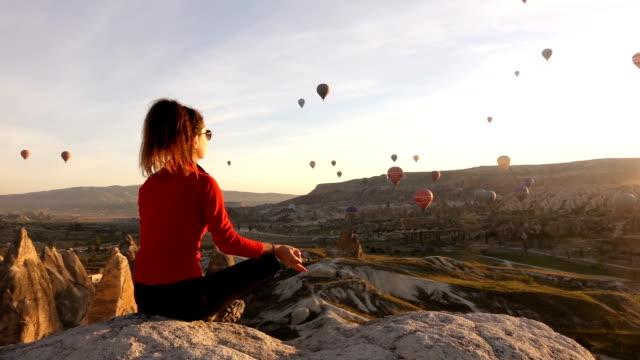 vídeos de stock e filmes b-roll de única mulher meditando enquanto vê balões de ar quente em cappadocia - mulher balões