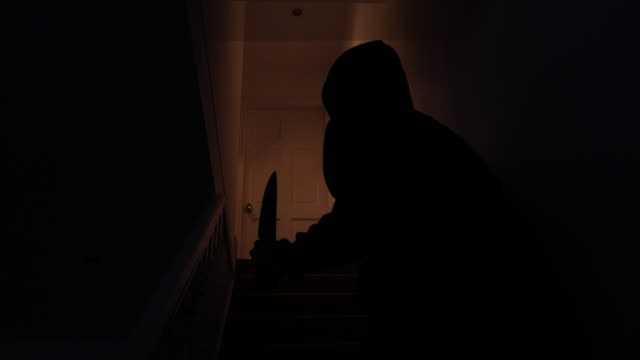 Sinister silhouette of a man with a knife breaking in to a home
