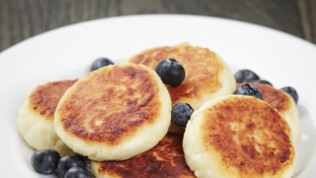 sirniki traditional russian pancakes from cottage cheese with blueberries sirniki traditional russian pancakes from cottage cheese with blueberries, shallow focus russian culture stock videos & royalty-free footage
