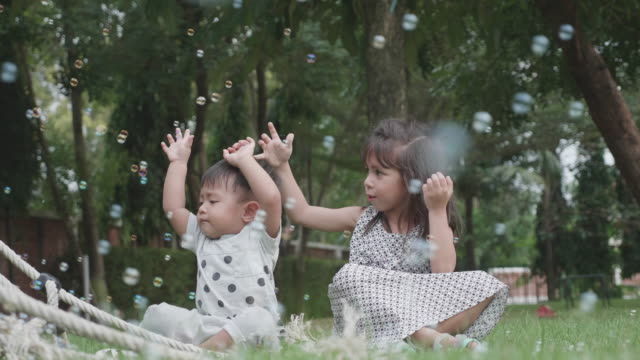 Sister and brother are having fun with soap bubbles.