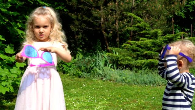 vídeos y material grabado en eventos de stock de hermana y hermano abrazar. dos niños, niño y niña con enormes gafas de sol - hermana