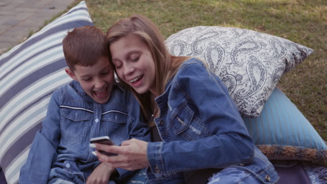 Sister and brother laughing and sharing a joke on their phone and having fun in a park video