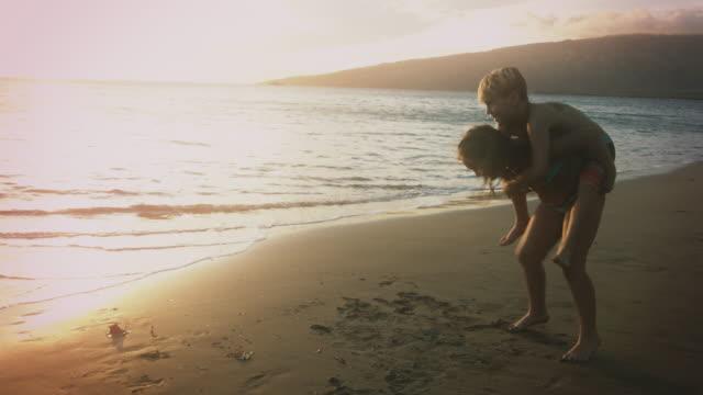 妹は、兄に海にピギーバック乗車を与えます。 - 兄弟点の映像素材/bロール
