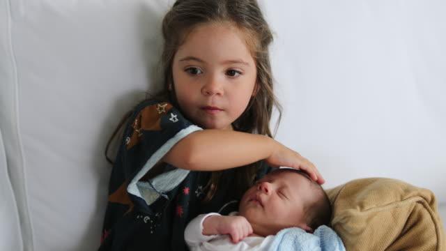 vídeos y material grabado en eventos de stock de hermana sosteniendo bebé recién nacido besos mostrando amor y afecto al hermano dormido - hermana