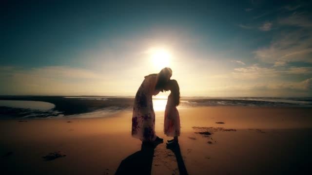 夕暮れ時のビーチでの抱擁で妹 - 抱きしめる点の映像素材/bロール