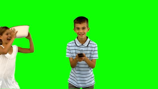 vídeos de stock e filmes b-roll de irmã verter pipoca sobre brothers cabeça - tv e familia e ecrã