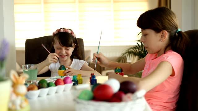 Hermanas para colorear huevos de Pascua en casa - vídeo