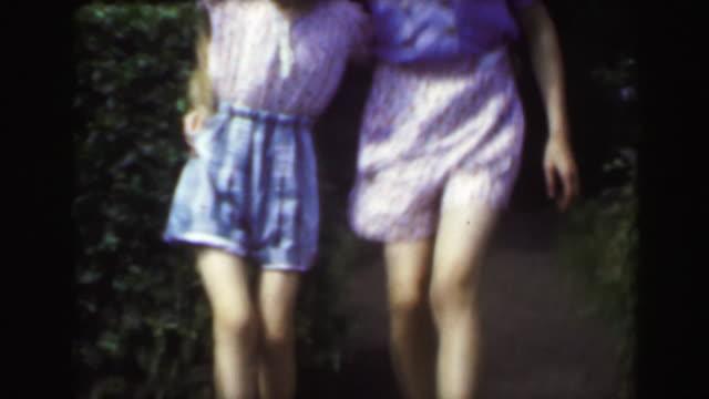 1949: Sisters dancing outdoor garden blond caucasian girls enjoying summer.