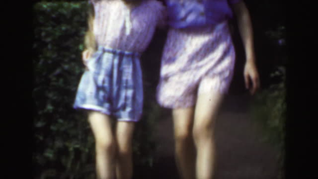 1949: Sisters dancing outdoor garden blond caucasian girls enjoying summer. video