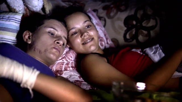 vídeos de stock e filmes b-roll de sisters eating snacks and watching a movie at home in the dark - tv e familia e ecrã