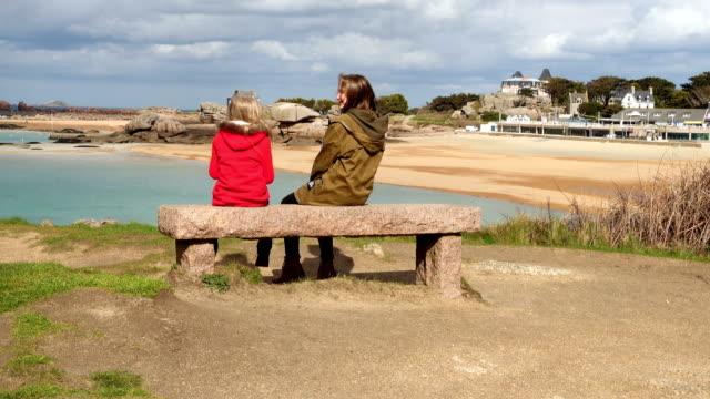 vidéos et rushes de sœurs filles assises sur un banc à la côte bretonne - bretagne