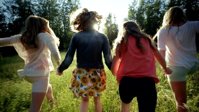 4 Sisters Hold Hands And Run In Slow Motion Through Meadow (Away From Camera) video
