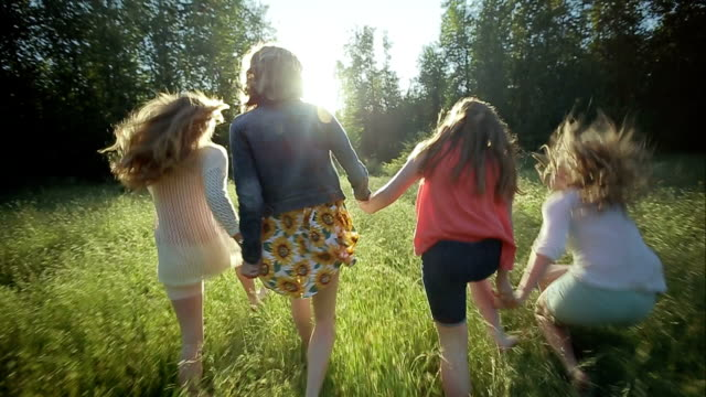 Sisters Hold Hands And Run Through A Field (Shot In Slow Motion) One Trips And Falls Down video