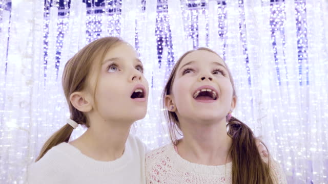 Sisters in fantasy lights at Christmas Sisters in wonder at the beautiful festive Christmas lights sister stock videos & royalty-free footage