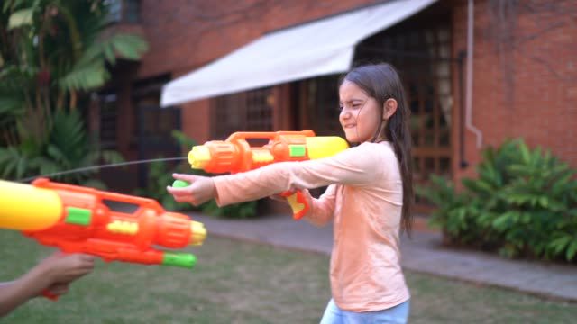 Sisters playing with squirt gun in backyard