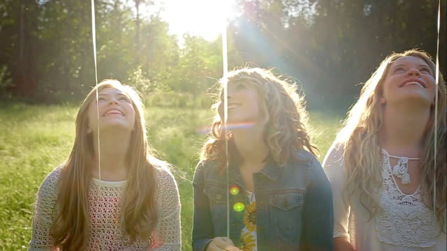 3 Sisters Sit In A Field And Look Up At Their Colorful Balloons (Camera Pans From Balloons Down To The Girls) video