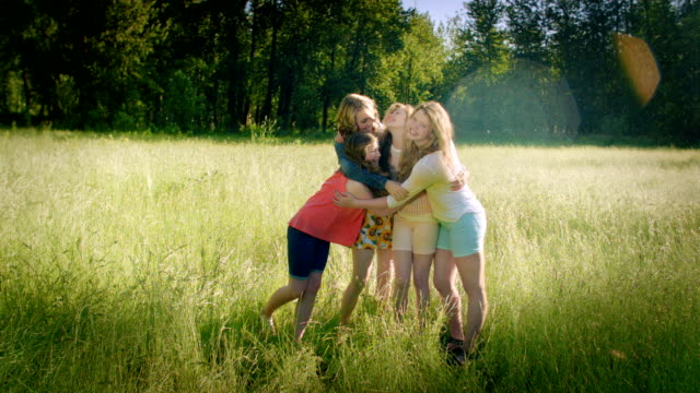 4 Sisters Stand In A Field And Hug, Oldest Sister Kisses Her Younger Sister On The Cheek video